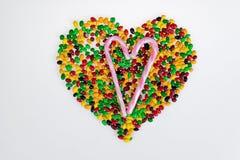 Coloured galaretowe fasole rozpraszają w formie menchii i białej serca i cukierki pasiasta trzcina na białym tle Fotografia Stock