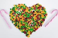 Coloured galaretowe fasole rozpraszają w formie menchii i białej serca i cukierki pasiasta trzcina na białym tle Fotografia Royalty Free