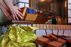 Coloured gift boxes near fireplace. Preparing gift boxes near fireplace during christmass time Royalty Free Stock Photography