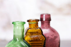 Coloured glass bottles on a rustic background Stock Photography