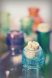 Coloured glass bottles on a rustic background Royalty Free Stock Photos