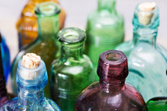 Coloured glass bottles on a rustic background Stock Photos
