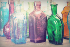 Coloured glass bottles on a rustic background Stock Images