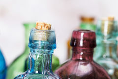 Coloured glass bottles on a rustic background Royalty Free Stock Photo