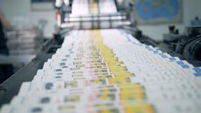 Coloured imprimió las revistas se está moviendo a lo largo de la banda transportadora almacen de metraje de vídeo