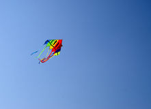 Coloured Kite in Sky. Multi coloured kite sailing up into the blue sky Royalty Free Stock Photography