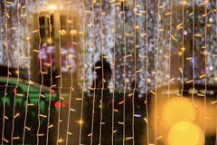 Free Coloured Light Bulbs. Christmas Street Decorations, New Year Preparation In City.Abstract Blurry Background Royalty Free Stock Photography - 128797537