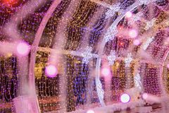 Coloured light bulbs and led snowflakes in light tunnel. Christmas street decorations, new year preparation in city. stock photography