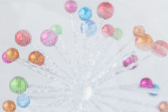 Coloured little Christmas balls behind transparent muslin material. Stock Photo