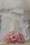A coloured macro photo of a detailed bouquet with pink roses, white small flowers and a fake diamond in the centre of the roses, t. He wedding dress is in the royalty free stock photos
