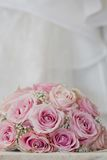 A coloured macro photo of a detailed bouquet with pink roses, white small flowers and a fake diamond in the centre of the roses, t. He wedding dress is in the royalty free stock photography