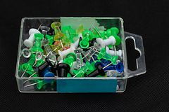 Coloured map-pins in a transparent container. Coloured map-pins in a plastic container isolated on a dark background stock photography
