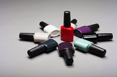Coloured nail polish bottles stacked circle. On a on a gray background closeup royalty free stock images