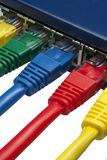 Coloured network plugs connected to router Stock Photos