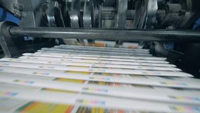 Coloured newspapers are moving along the belt. 4K stock video footage