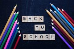 Coloured ołówki wokoło drewnianych słów szkoła na łupkowym czarnym tle z powrotem tylna koncepcji do szkoły Odgórny widok fotografia stock