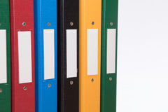 Coloured office document folders with blank labels. Close up of a row of multicoloured office document folders with blank labels and plain white background with Royalty Free Stock Photography