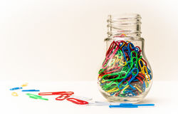 Coloured Paper Clips in a Container. Bright coloured paper clips in a decorative light bulb, screw top jar. Isolated on a white background Stock Photography