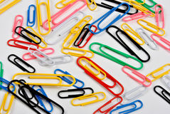 Coloured paper clips and a white background Royalty Free Stock Images
