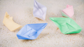 Coloured Paper Ships Chaotic Laying on Sandy in the Desert.  Stock Photo