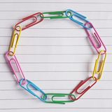 Coloured paperclips in a circle on lined paper royalty free stock photo