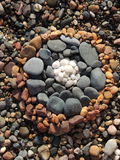 Coloured pebble circle on a beach. Pebbles arranged in circles ordered by colour Royalty Free Stock Images