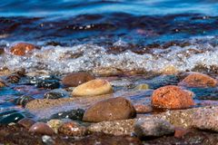 Coloured pebbles at the shoreline with water and waves royalty free stock photo
