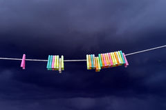 Coloured pegs & stormy sky. Coloured clothes pegs on a line against a dark brooding sky Royalty Free Stock Photography