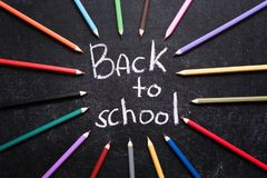 Coloured pencils around Back to School words on slate black background. Back to school concept. Top view. Stock Image