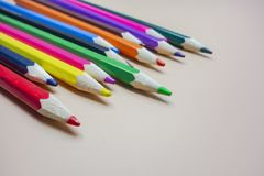 Coloured pencils arranged neatly. In a green background stock image