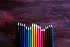 Coloured pencils on brown background. Coloured pencils in a row on brown background stock photo
