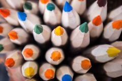 Coloured wooden pencils close up. Coloured pencils top view with selective focus on central pencil stock images