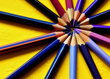 Coloured pencils. Palette of colored pencils in vibrant blue and violet tones on a vibrant paper textured yellow background Stock Image