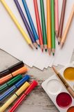 Coloured pencils on paper with felt-tip pens and watercolor beside. Coloured pencils on paper with felt-tip pens, watercolor and brush beside. Wooden table. Top royalty free stock photos
