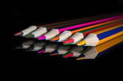 Coloured pencils on a reflective glass mirror surface royalty free stock photography