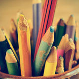 Coloured pencils, with a retro effect. Closeup of some wooden coloured pencils of different colors in a pencil pot, with a retro effect Royalty Free Stock Image