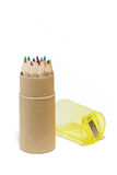 Coloured pencils in a round box. Several coloured pencils in a round cardboard box, isolated on white background royalty free stock photos