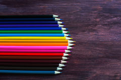 Coloured pencils. In a row on dark background royalty free stock photography