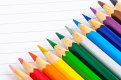 Coloured Pencils. Row of Coloured Pencils on a Sheet of paper royalty free stock images