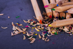 Coloured pencils and shavings against a black background Stock Photos