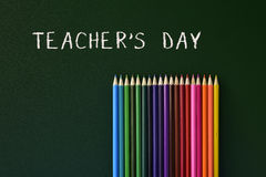 Coloured pencils and text teachers day written in a green chalkb. Some coloured pencils of different colors and the text teachers day written in a green Royalty Free Stock Image