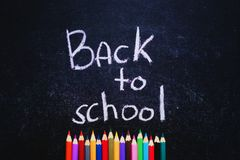Coloured pencils under Back to School words on slate black background. Back to school concept. Top view. Stock Photo