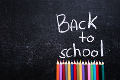 Coloured pencils under Back to School words on slate black background. Back to school concept. Top view. Free space Royalty Free Stock Images