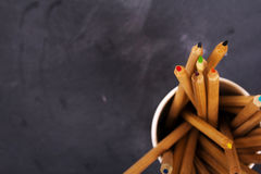 Coloured pencils on a worn black background Royalty Free Stock Images