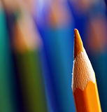Coloured pencils. Yellow colored pencil separated on a cool blue and green blurred  background Stock Image