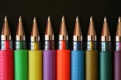 Coloured Pens. A line of coloured pens on a black background stock images