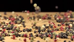 coloured pepper peppercorns pouring on wooden board. spices and food ingredients. shallow depth of field