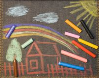 Coloured pieces of chalk. And children pictureon jeans fabric royalty free stock photo