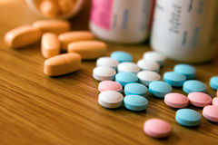 Coloured Pills. Closeup pink, white, blue and orange vitamins with bottles Royalty Free Stock Image