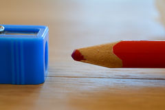 Coloured red pencil and sharpener on wooden table. Stock Images